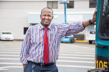 Photo of Abdi Elmi, Metro base chief, standing next to a Metro bus